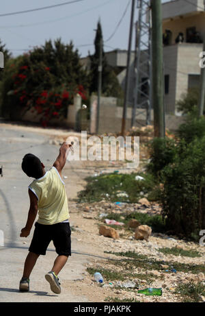 August 31, 2018 - Palestinian children and teenagers clash with the Israeli Security Forces during a weekly protest in the West Bank town of Kafr Qaddum against the confiscation of land and the closure of the town's main road. The issue of Israel constantly seizing land to build or extend Israeli settlements in the West Bank is a major stumbling block in the achievement of a peace settlement between the Palestinians and the Israelis.  The residents of Kafr Qaddum have been holding weekly demonstrations since 2011 in protest against the extension of the nearby Israeli settlement of Kadumin, t - Stock Photo