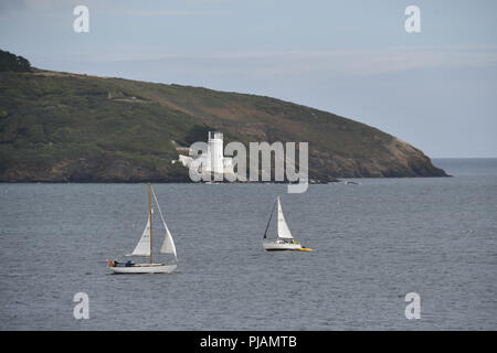 Two yachts sailing towards each other on the sea at Falmouth with St Anthonys lighthouse in the background. - Stock Photo