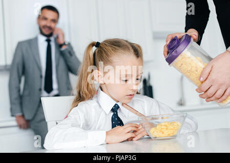 selective focus of kid in school uniform at table with breakfast and parents at home, back to school concept - Stock Photo