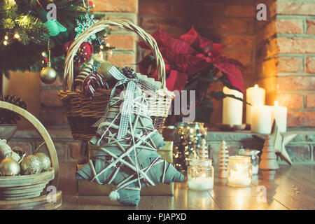 Christmas setting background, decorated Christmas tree, pine cones in the basket, wooden trees, poinsettia with fireplace on the background, candles a - Stock Photo