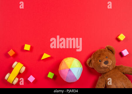 Baby kids toys background. Teddy bear, wooden car, colorful bricks on red background - Stock Photo