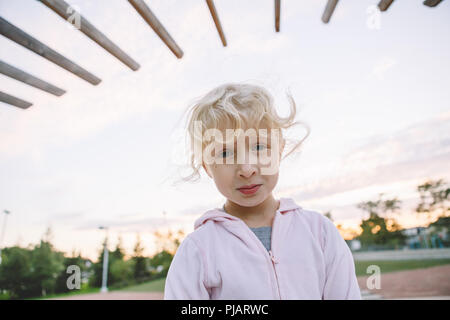 Upset baby. Portrait of cute adorable little blonde Caucasian girl child making funny silly faces. Kid playing having fun in park outside at sunset. T - Stock Photo