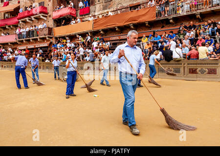 City Workers Sweep The Track Before The Start Of The Race, Piazza Del Campo, The Palio di Siena, Siena, Italy - Stock Photo