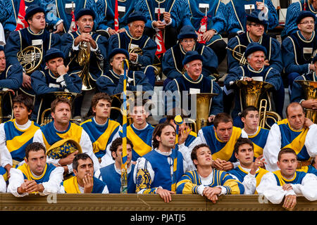 Colourfully Dressed Musicians and Contrada Members Wait Nervously For The Start Of The Palio In The Piazza Del Campo, The Palio di Siena, Siena, Italy - Stock Photo