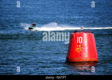 Purbeck, Dorset, UK - Jun 02 2018: Man on a jet ski speeding past a 10 knot speed limit marker buoy - Stock Photo