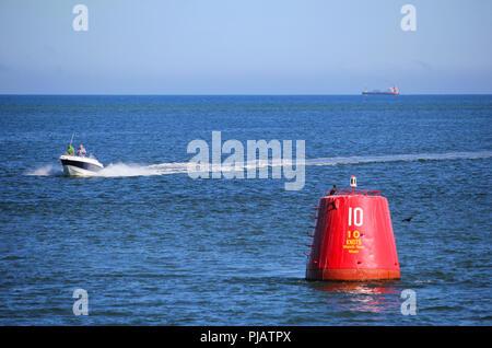 Purbeck, Dorset, UK - Jun 02 2018: Motorboat speeding past a 10 knot speed limit marker buoy - Stock Photo