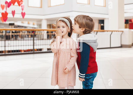 Group portrait of two white Caucasian cute adorable funny children boy and girl talking telling secrets to each other. Love friendship fun concept. Be - Stock Photo