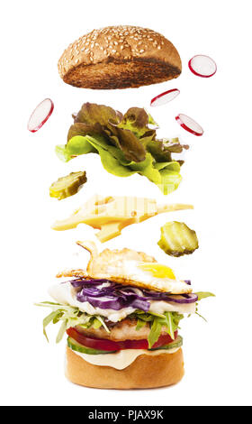 Big tasty homemade burger with flying ingredients - Stock Photo