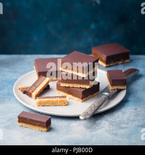 Chocolate caramel slices, bars, millionaires shortbread on a plate. Blue background. Copy space. - Stock Photo