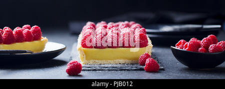 Raspberry tart with vanilla custard and white chocolate on slate board. Black stone background. Copy space. - Stock Photo