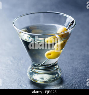 Martini cocktail with green olives. Slate background. Close up. - Stock Photo