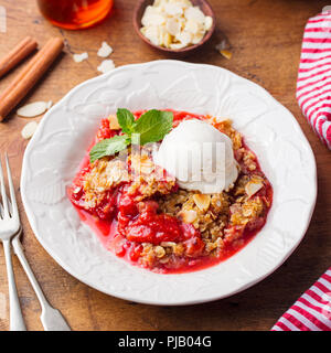 Crumble with berries and fruits with vanilla ice cream. Close up. - Stock Photo