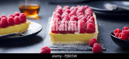 Raspberry tart with vanilla custard and white chocolate on slate board. Black stone background. - Stock Photo
