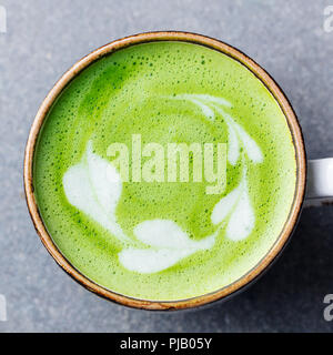 Matcha, green tea latte in a cup. Grey stone background. Close up. Top view. - Stock Photo