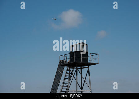 A United Nations helicopter fly over a watchtower apparently built by the Lebanese army on the Israeli-Lebanese border near Rosh HaNikra Crossing also known as Ras Al Naqoura Crossing. - Stock Photo
