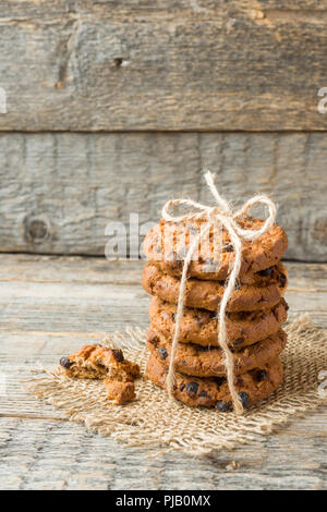 Homemade cookies with chocolate thread tied on a wooden table. - Stock Photo