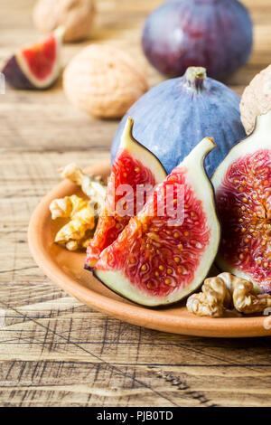 Fresh figs whole and cut kernels of walnuts on a plate the old wooden background - Stock Photo