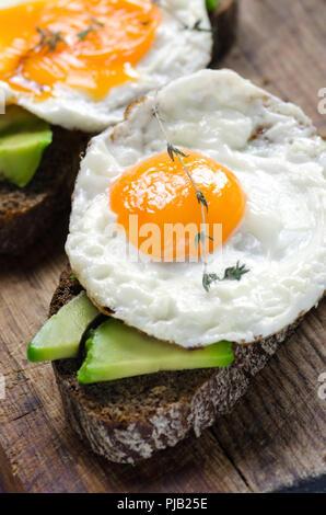 Healthy breakfast. Sandwich with rye bread, avocado and fried eggs. - Stock Photo