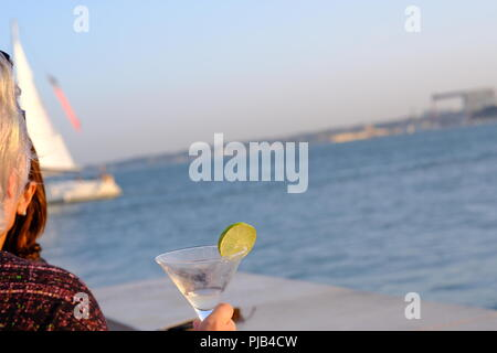 Cocktail in glass with slice of lime against the backdrop of the Tolgus river in Lisbon - Stock Photo