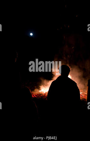 silhouettes of people around a large bonfire underneath a nearly full moon on a winter's night in the Cevennnes, France - Stock Photo