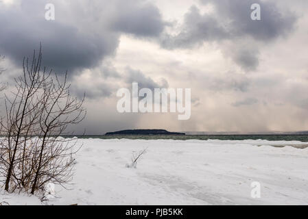 Scenic winter view from the ice and snow covered shore of Grand Traverse Bay (Lake Michigan) looking toward Power Island. - Stock Photo
