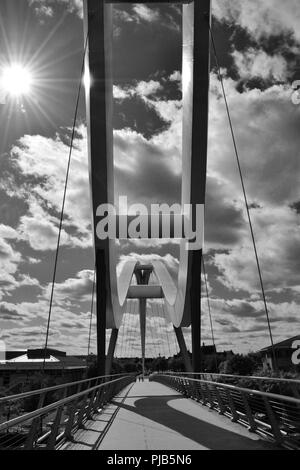 Striking black and white, naturally lit image of the iconic Infinity Bridge spanning the River Tees in Stockton-on-Tees, UK. - Stock Photo