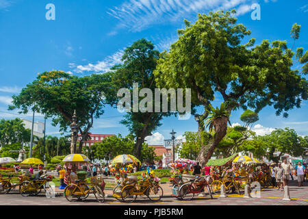 Tourists strolling along nicely decorated yellow trishaws near the fountain at the Dutch Square (Stadthuys area) under trees shade on a beautiful... - Stock Photo