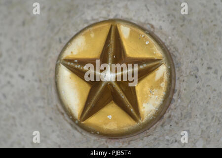 A nice close-up of a five-pointed metal star on a circle embedded in concrete. The gold colour faded a bit.