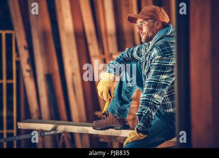 Satisfied Caucasian Carpenter Portrait. Woodworking Worker Relaxing After Full Day of Hard Work. - Stock Photo