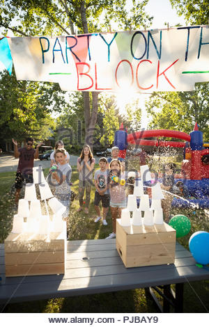 Kids playing water game at summer neighborhood block party in sunny park - Stock Photo