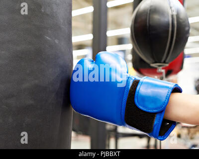 Hand of a child in a boxing glove and punching bag - Stock Photo
