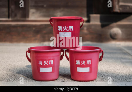 Japanese traditional fire prevention water red platic bucket in front of a wooden temple. - Stock Photo