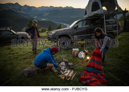 Friends camping, preparing campfire on remote mountain hilltop - Stock Photo
