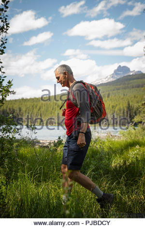 Mature man backpacking, hiking in sunny forest along lake - Stock Photo