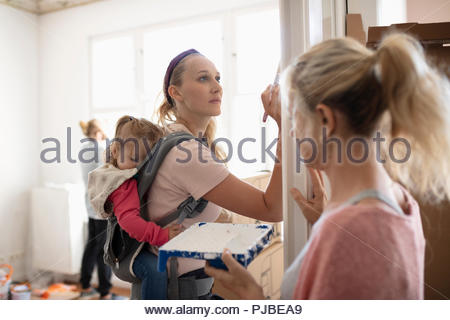 DIY mother painting with sleeping baby daughter in baby carrier - Stock Photo