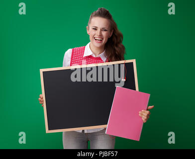 smiling young student woman in a red waistcoat with book showing blackboard against green background - Stock Photo