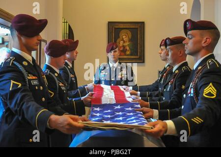The flag of the United States is folded over the casket of the late retired 1st Sgt. Harold Eatman by paratroopers of the 2nd Battalion, 505th Parachute Infantry Regiment on July 11, 2018 at the Cathedral of Saint Patrick in Charlotte, North Carolina as 1st Sgt. James Miller of Company B, 2-505 PIR, center, looks on.  Eatman was a member of the 505th PIR and conducted four World War II combat jumps into Sicily, Salerno, Normandy and Holland with the regiment.  He died earlier in July at the age of 102. - Stock Photo