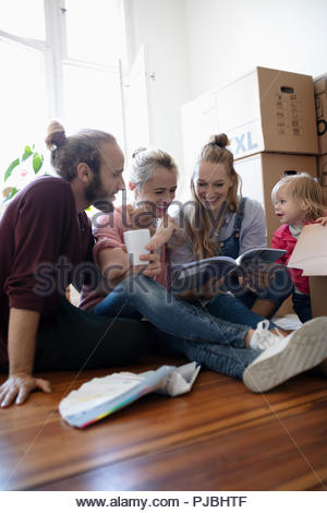 Multi-generation family reading book, taking a break from moving - Stock Photo