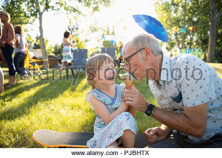 Father tasting daughters ice cream cone at summer neighborhood block party in park - Stock Photo