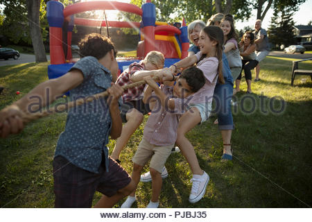 Kids and neighbors playing tug-of-war at summer neighborhood block party in park - Stock Photo