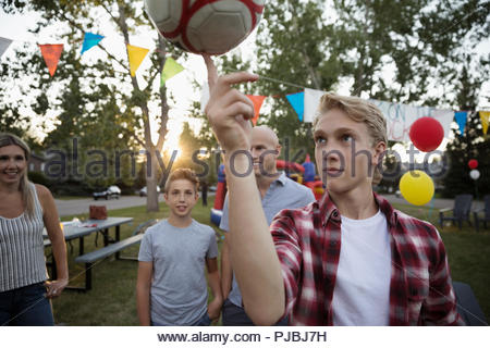 Boy balancing soccer ball on finger at summer neighborhood block party in park - Stock Photo
