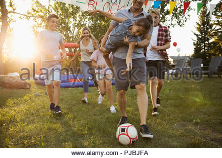 Playful family playing soccer at summer neighborhood block party in sunny park - Stock Photo