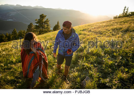 Couple with coffee and blanket walking on sunny, idyllic mountain hillside, Alberta, Canada - Stock Photo