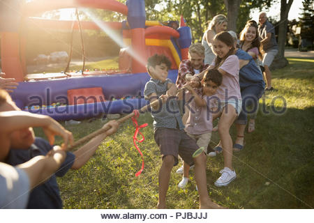 Kids playing tug-of-war at summer neighborhood block party in sunny park - Stock Photo
