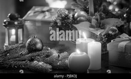 Black and white image of beautiful Christmas decorations and candles on wooden table - Stock Photo