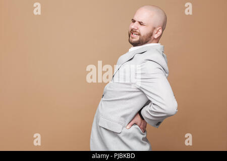 Back spine pain. Profile side view portrait of middle aged bald bearded businessman in light gray suit standing and touching his painful spin. indoor  - Stock Photo