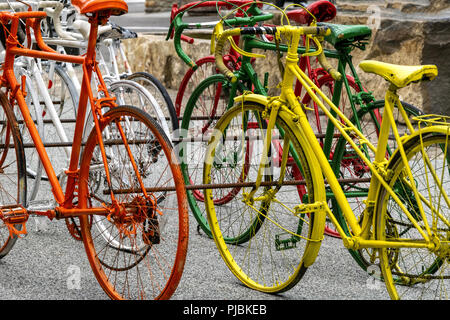 Street Art, old bicycles, different colors, seems to be racing each other without riders.   French Town, Tour de France, Art Installation,  Yellow ... Stock Photo