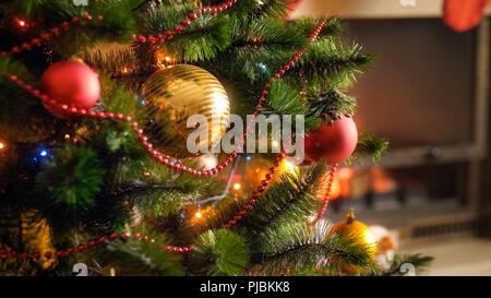 Closeup image of decorated Christmas tree branches against burning fireplace in living room at house - Stock Photo