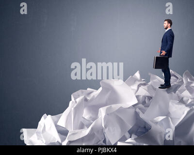 Thoughtful young businessman standing on a pile of crumpled paper with a light grey background - Stock Photo