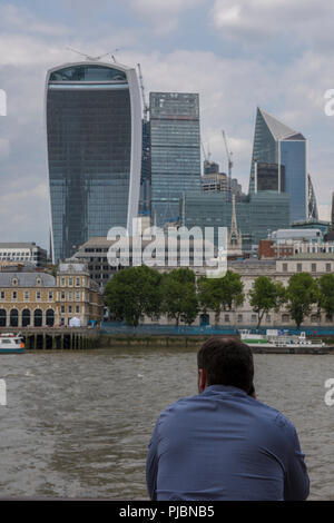 man looking across the river thames in central london towards the city of london. - Stock Photo